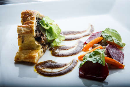 closeup modern dish of baked in dough meat with mushrooms and spinach decorated with salad leaves and brown sauce on white plate