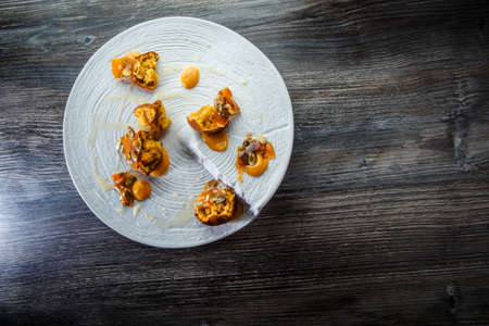top view on trendy restaurant dessert of crushed cupcakes with sweet sauce and caramelized pumpkin seeds on white plate on wooden table Imagens