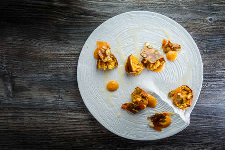 top view on exclusive restaurant dessert of crushed cupcakes with sweet sauce and caramelized pumpkin seeds on white plate on wooden table