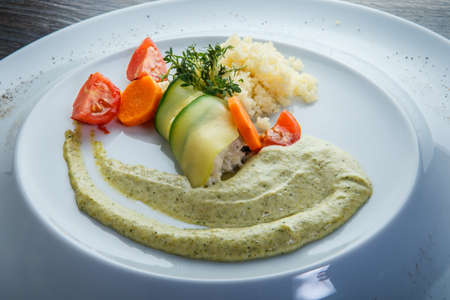 closeup rice and sliced vegetables trendy decorated with green sauce and greens served in white restaurant plate on wooden table Archivio Fotografico