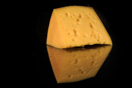 big wedge of hard porous yellow cheese with holes on black mirror background with reflection and copy space 版權商用圖片