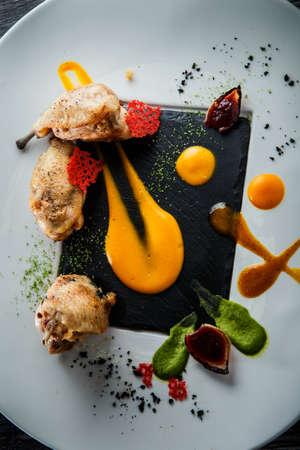 Vista vertical superior closeup restaurante moderno plato de patas de codorniz asadas decoradas con una variedad de salsas en la placa blanca sobre la mesa de madera Foto de archivo