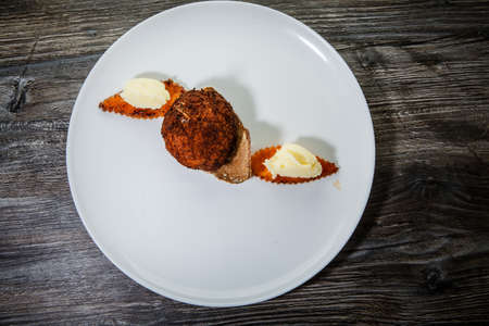top view on finely decorated chicken kiev cutlet with mashed potato garnish and dark bread slice on white restaurant plate on wooden table