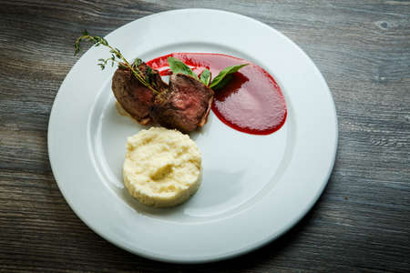 top view on tasty barbecued meat pieces served with potato puree garnish and red sauce on white restaurant plate on dark wooden table
