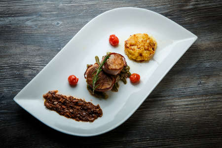 top view on conceptual restaurant dish of fried meat with mushroom sauce and cheese casserole on original plate on wooden table