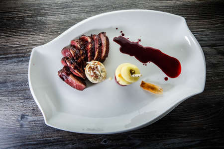 top view on restaurant dish of roasted sliced duck breast with apple, garnish and red sauce on modern white plate on wooden table