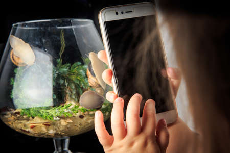 closeup small girl take phone picture of snails in big glass wineglass against black background