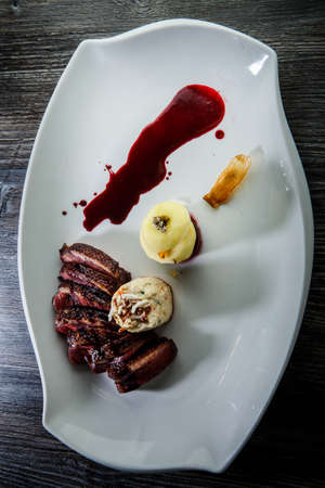 vertical view on restaurant dish of baked sliced duck breast with apple, garnish and red sauce on modern white plate on wooden table