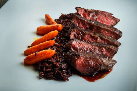 closeup restaurant dish of barbecued sliced meat served with wild rice and grilled carrot garnish on original white plate on wooden table