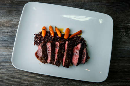 top view on tasty restaurant dish of barbecued sliced meat with wild rice and grilled carrot garnish on modern white plate on wooden table
