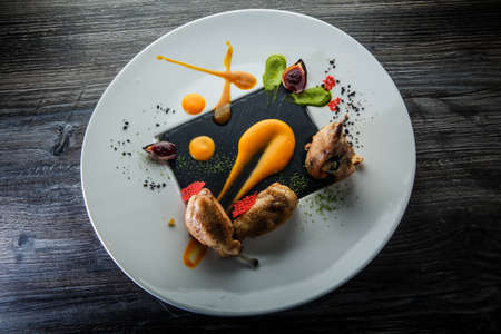 top view on modern restaurant dish of roasted quail legs decorated with assorted sauces on round white plate on wooden table