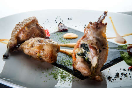 closeup roasted quail legs with green spinach filling decorated with assorted sauces on modern plate against white background