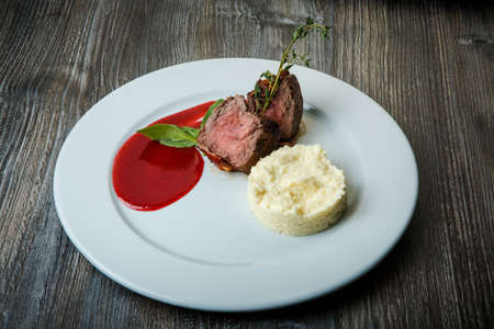 finely decorated restaurant dish of roasted meat pieces served with mashed potato garnish and red sauce on white plate on wooden table 写真素材