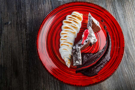 top view on sliced homemade brownie cake with baked white cream and chocolate sauce on restaurant plate on wooden table