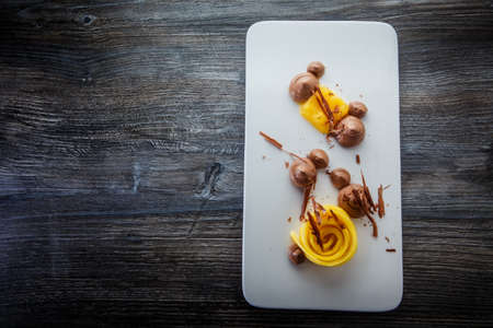 top view tasty homemade fruit and chocolate mousse dessert served on white original plate on wooden table plate