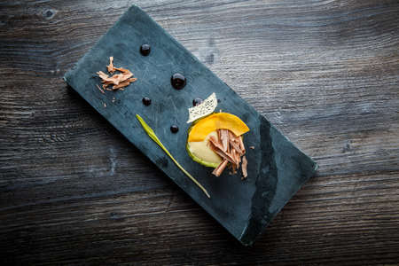 top view on original dessert of baked avocado decorated with chocolate slices, cream sauce, and syrup served on black stone board on wooden table 写真素材