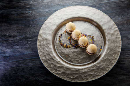 finely decorated with flowers four spherical sponge biscuits with caramel filling served on golden plate on wooden table