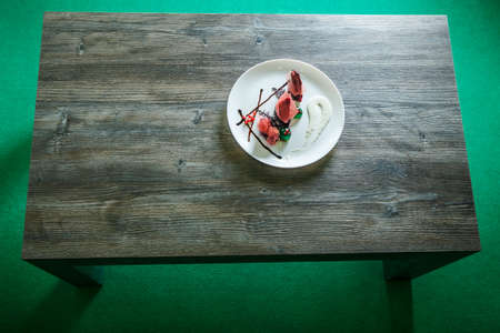 top view on white round restaurant plate with beautiful dessert stands on dark wooden table on green background