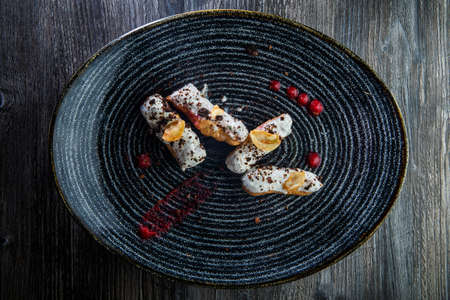 four fresh delicious eclairs with white topping and chocolate decoration on original black restaurant plate