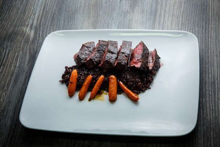 trendy restaurant dish of barbecued sliced meat served with wild rice and grilled carrot garnish on modern white plate on wooden table 写真素材 - 132590269