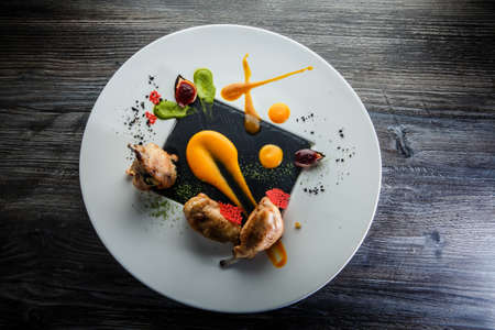 top view on original restaurant dish of fried quail legs decorated with assorted sauces on round white plate on dark wooden table Фото со стока