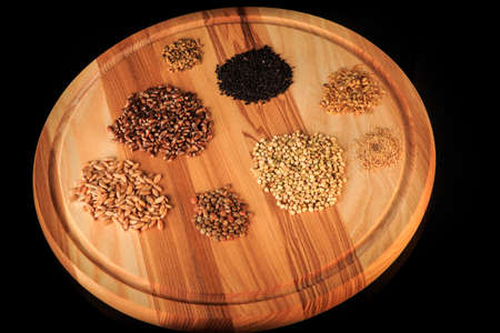 closeup round wooden board with assorted groat handfuls flax, wheat, buckwheat, black quinoa, millet grains on black