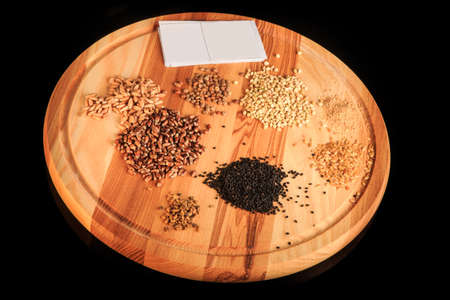 wooden board with assorted groat handfuls flax, wheat, buckwheat, black quinoa, millet grains and white visit card 写真素材 - 132590329