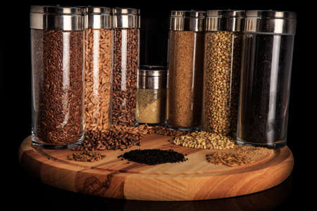 assorted organic grains of flax, wheat, green buckwheat, millet groats in tall glass jars on wooden board against black 写真素材