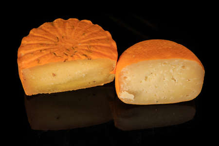 top view of two halves of different hard porous yellow cheese heads with holes on black mirror background