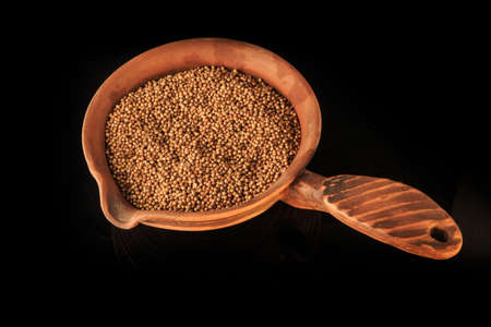 dried organic aromatic coriander seeds in handmade clay bowl isolated on black background 写真素材 - 132828675