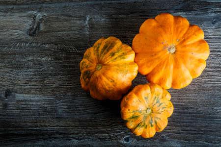top view closeup three decorative orange pumpkins of different sizes on dark wooden table background