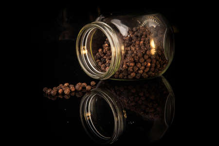 dried dark whole pepper peas poured from round glass jar on black mirror surface with reflection