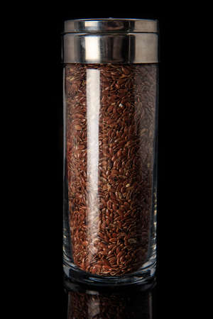 closeup organic flax seeds in tall glass jar with metal cap isolated on black background