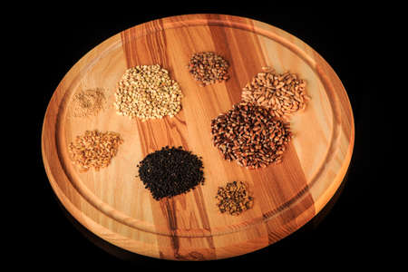 top view on wooden board with assorted groat handfuls flax, wheat, green buckwheat, black quinoa, millet grains on black