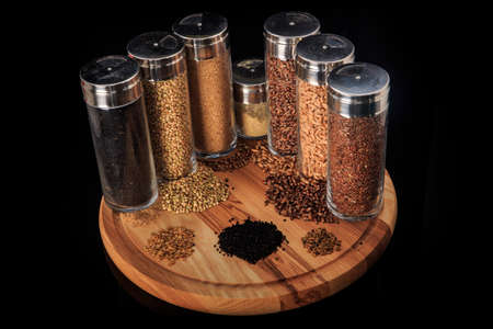 top view on assorted groats of flax, wheat, green buckwheat, millet grains in tall glass jars on wooden board against black