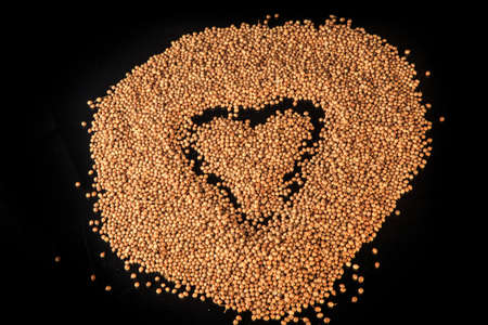 top view on heart sign made in big heap of dried organic coriander seeds isolated on black background 写真素材