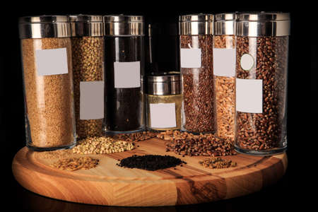 closeup assorted groats of flax, wheat, green buckwheat, millet grains in tall glass jars on wooden board against black