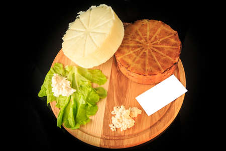 top view of wooden board with white visit card and two whole heads of homemade cheese on black background