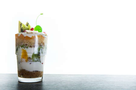 mousse cream and fruits dessert with sliced kiwi and green jelly cherry served in glass against white background 写真素材 - 132899351