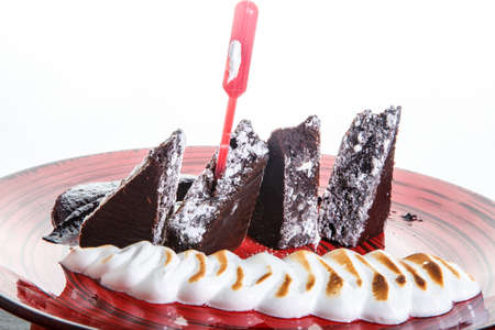 closeup sliced homemade brownie cake with baked white cream and chocolate sauce on red plate against white background 写真素材