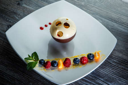 beautiful white and black chocolate ball dessert served with assorted berries on restaurant plate on wooden table 写真素材 - 132900963