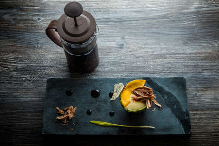 top view on exquisite dessert of baked avocado with chocolate slices, cream sauce served on black stone board and with tea spot on wooden table