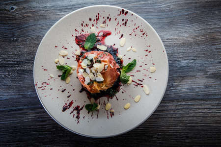 top view on delicious baked apple decorated with fruit syrop, nuts and mint on restaurant plate on wooden table 写真素材