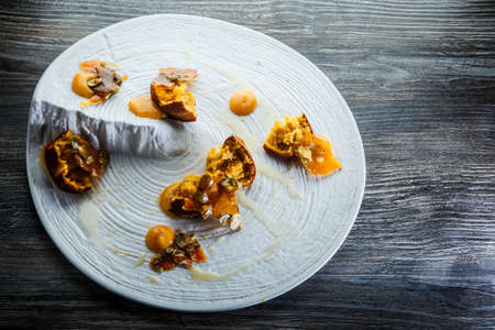 delicious original restaurant dessert of crushed cupcakes with sweet sauce and caramelized pumpkin seeds on white plate on wooden table