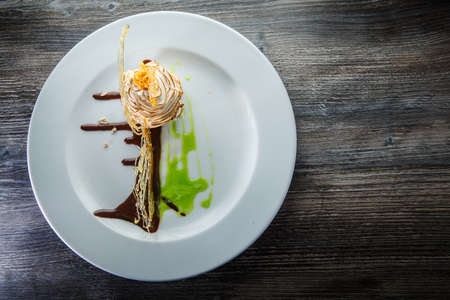 top view on delicious baked swan-shaped cream dessert with chocolate and caramel decoration on round restaurant plate 写真素材 - 132909294