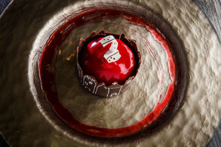 top view closeup trendy red mirror glazed mousse cake in apple shape with caramel dressing on round gold restaurant plate