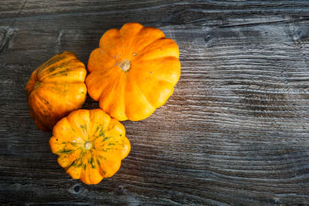 top view closeup assorted decorative yellow pumpkins of different sizes on dark wooden table background 写真素材