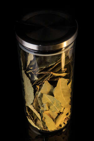 top view on organic dried bay leaves in tall glass jar with metal cap isolated on black background 写真素材