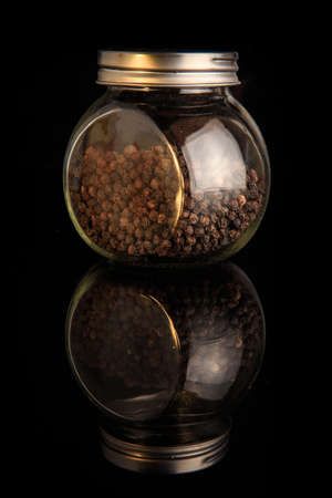 organic dried pepper peas in round glass jar with metal cap served on black mirror background with reflection 写真素材 - 133014308