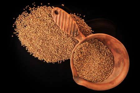 top view of dried aromatic coriander seeds in handmade clay bowl and near isolated on black background